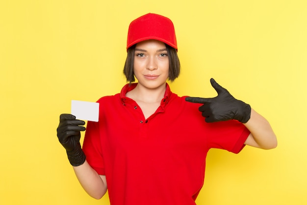 Widok z przodu młoda kobieta kurier w czerwone jednolite czarne rękawiczki i czerwoną czapkę