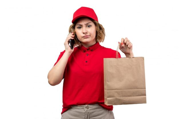 Widok z przodu młoda kobieta kurier w czerwonej koszuli czerwona czapka gospodarstwa pakiet dostawy rozmawia przez telefon