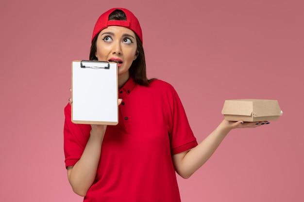 Widok z przodu młoda kobieta kurier w czerwonej pelerynie munduru z małym pakietem żywności dostawy i notatnikiem na rękach myśląc na różowej ścianie