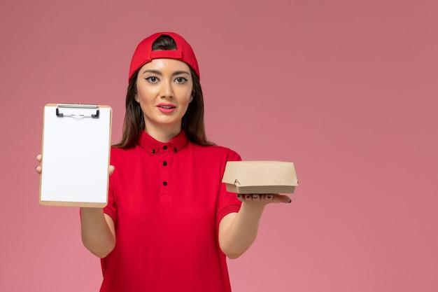 Widok z przodu młoda kobieta kurier w czerwonej pelerynie munduru z małym pakietem żywności dostawy i notatnikiem na rękach na różowej ścianie