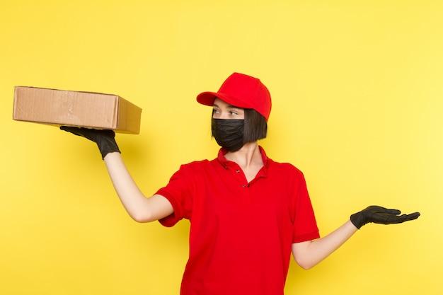 Widok z przodu młoda kobieta kurier w czerwonym mundurze czarne rękawiczki, czarna maska i czerwona czapka trzyma pudełko na żywność