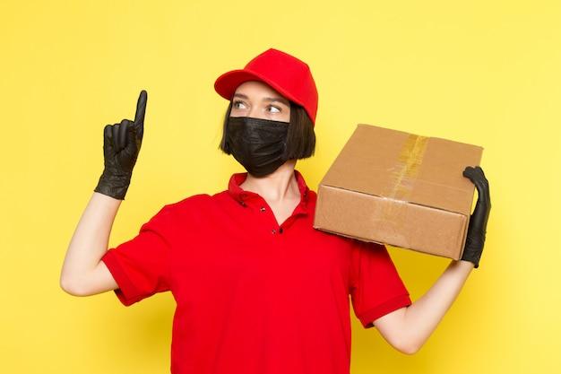 Widok z przodu młoda kobieta kurier w czerwonym mundurze czarne rękawiczki maska i czerwona czapka trzyma pudełko na żywność