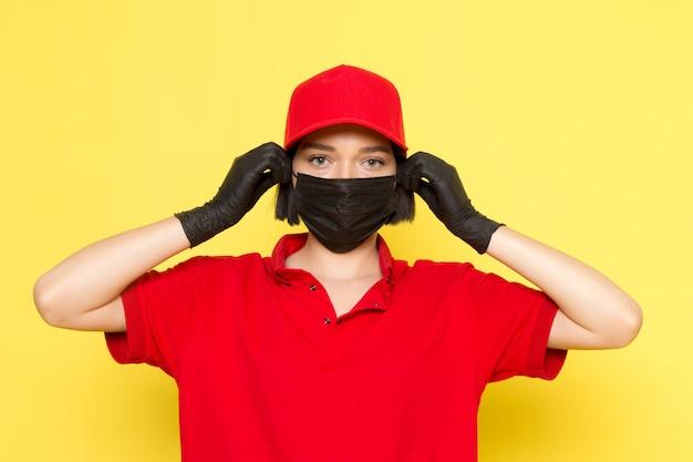 Widok z przodu młoda kobieta kurier w czerwonym mundurze, czarnych rękawiczkach, czarnej masce i czerwonej czapce