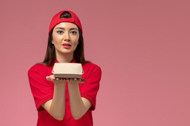 Widok z przodu młoda kobieta kurier w czerwonym mundurze i pelerynie z małym pakietem żywności dostawy na rękach na jasnoróżowej ścianie