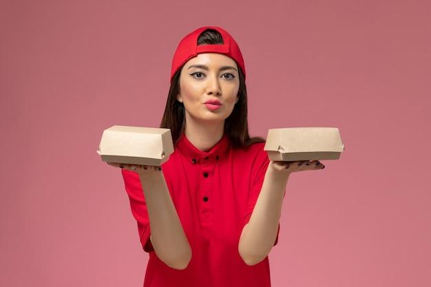 Widok z przodu młoda kobieta kurier w czerwonym mundurze i pelerynie z małymi paczkami żywności dostawy na rękach na różowej ścianie