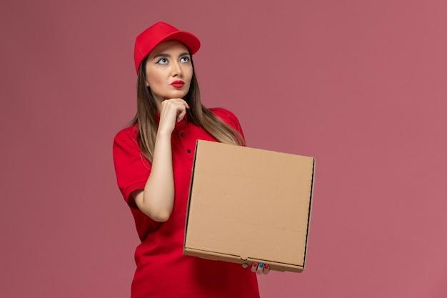 Widok z przodu młoda kobieta kurier w czerwonym mundurze trzymając dostawę pudełko z jedzeniem myśli na różowym tle firma świadcząca usługi