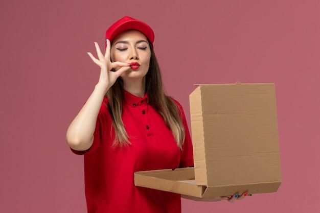 Widok z przodu młoda kobieta kurier w czerwonym mundurze, trzymając puste pole dostawy żywności na różowym tle usługi dostawy pracy firma mundurowa