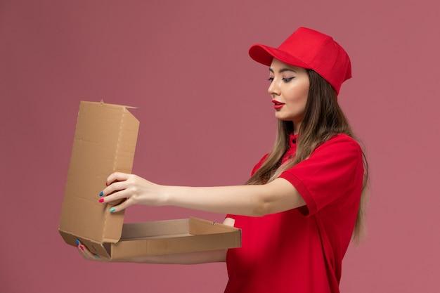 Widok z przodu młoda kobieta kurier w czerwonym mundurze, trzymając puste pole pożywienia na różowym tle firma świadcząca usługi w mundurze