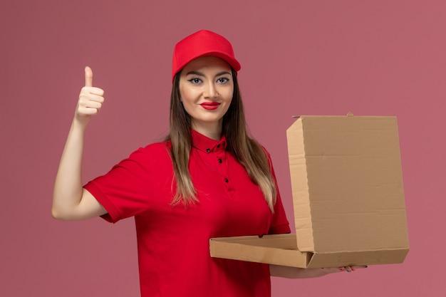 Widok z przodu młoda kobieta kurier w czerwonym mundurze, trzymając puste pudełko dostawy żywności i uśmiechając się na różowym tle firma usługowa dostawa pracy