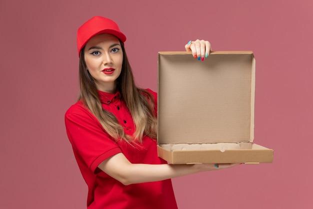 Widok z przodu młoda kobieta kurier w czerwonym mundurze, trzymając puste pudełko po żywności na jasnoróżowym tle firma świadcząca usługi w mundurze