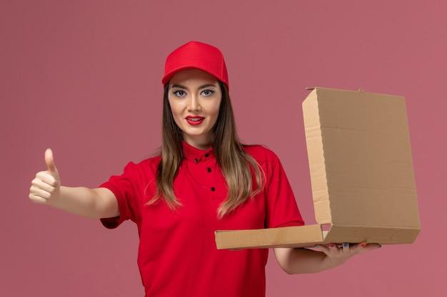 Widok z przodu młoda kobieta kurier w czerwonym mundurze, trzymając puste pudełko z jedzeniem dostawy z uśmiechem na jasnoróżowym tle
