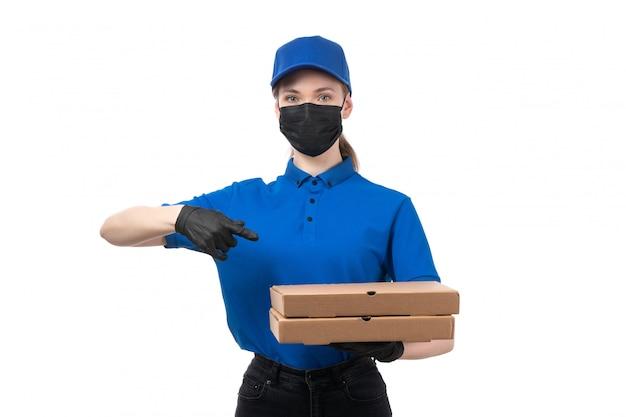 Widok z przodu młoda kobieta kurier w niebieskie jednolite czarne rękawiczki i czarną maskę trzyma paczki z dostawą żywności
