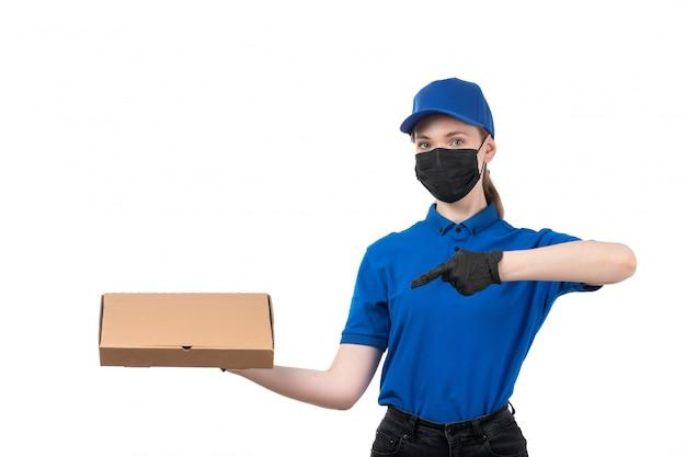 Widok z przodu młoda kobieta kurier w niebieskie jednolite czarne rękawiczki i czarną maskę trzyma pakiet dostawy żywności