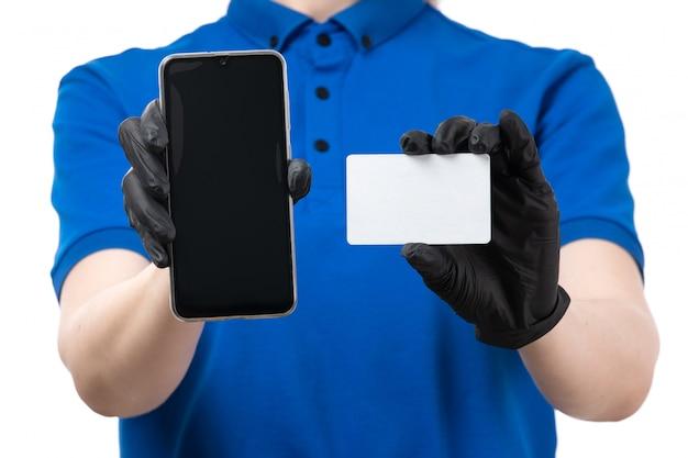 Widok z przodu młoda kobieta kurier w niebieskie jednolite czarne rękawiczki i czarną maskę trzymając telefon i białą kartę