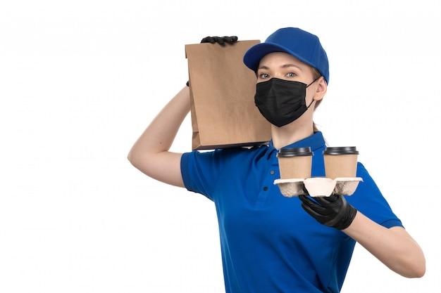Widok z przodu młoda kobieta kurier w niebieskiej jednolitej czarnej masce i rękawiczkach, trzymając filiżanki i opakowanie
