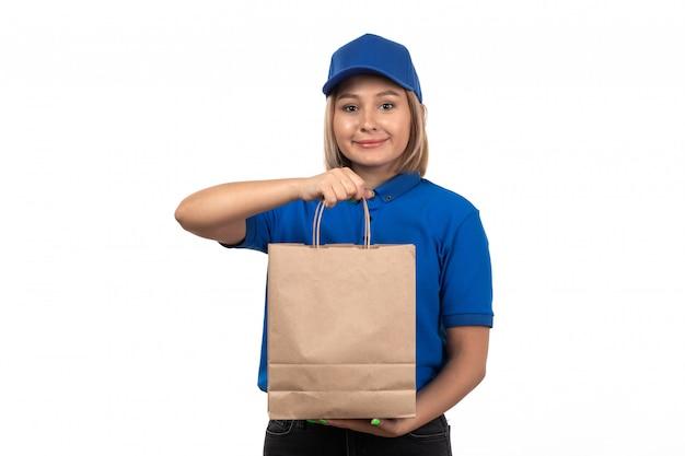 Widok z przodu młoda kobieta kurier w niebieskim mundurze gospodarstwa pakiet dostawy żywności