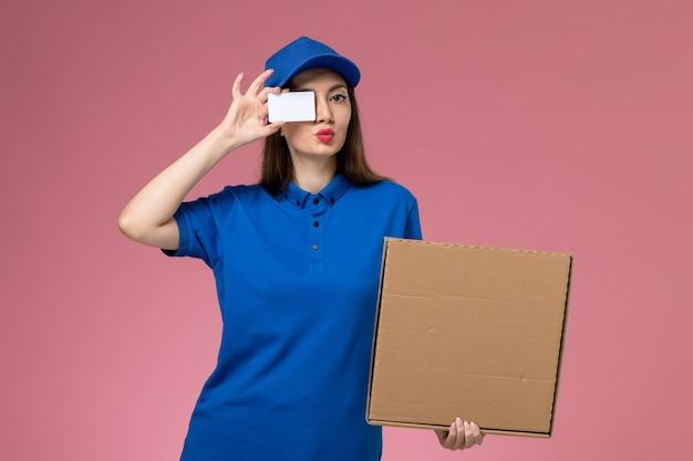Widok z przodu młoda kobieta kurier w niebieskim mundurze i pelerynie trzyma pudełko z jedzeniem i kartę na różowej ścianie pracownika