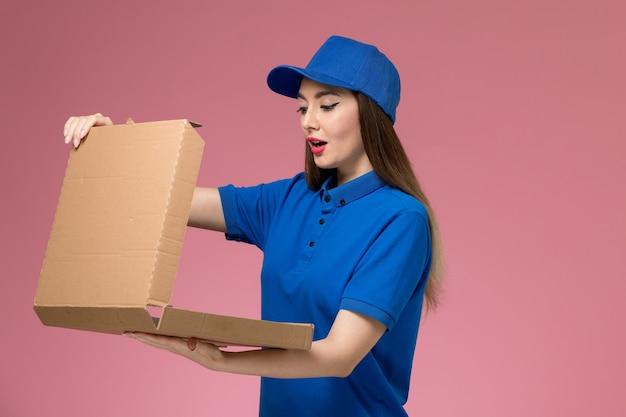 Widok z przodu młoda kobieta kurier w niebieskim mundurze i pelerynie trzyma pudełko z jedzeniem, otwierając je na różowym biurku