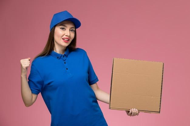 Widok z przodu młoda kobieta kurier w niebieskim mundurze i pelerynie, trzymając pudełko dostawy żywności na jasnoróżowej ścianie