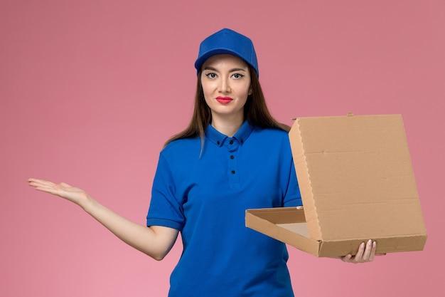 Widok z przodu młoda kobieta kurier w niebieskim mundurze i pelerynie, trzymając pudełko dostawy żywności, otwierając ją uśmiechając się na różowej ścianie