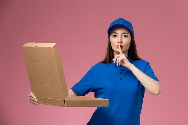 Widok z przodu młoda kobieta kurier w niebieskim mundurze i pelerynie trzymająca pudełko z dostawą żywności na jasnoróżowej ścianie usługi pani dostawy jednolita praca