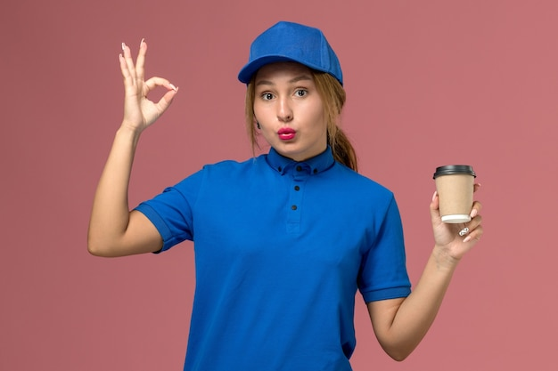 Widok z przodu młoda kobieta kurier w niebieskim mundurze, pozowanie, trzymając brązową filiżankę kawy na różowej ścianie, mundurowa kobieta dostawy