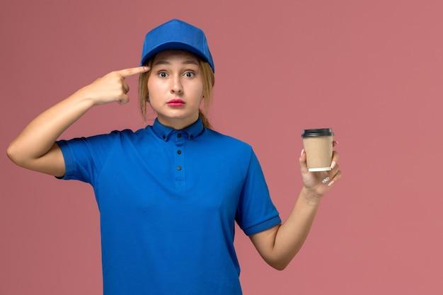 Widok z przodu młoda kobieta kurier w niebieskim mundurze pozowanie, trzymając brązowy dostawy filiżankę kawy, mundur usługowy dostawy kobieta pracownik praca