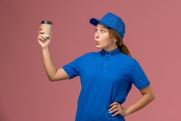 Widok z przodu młoda kobieta kurier w niebieskim mundurze, pozowanie, trzymając dostawę filiżankę kawy na różowej ścianie usługi pracy jednolita kobieta dostawy