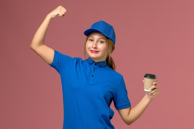 Widok z przodu młoda kobieta kurier w niebieskim mundurze pozowanie, trzymając filiżankę kawy, mundur usługowy dostawy zdjęcie pracownika pracy