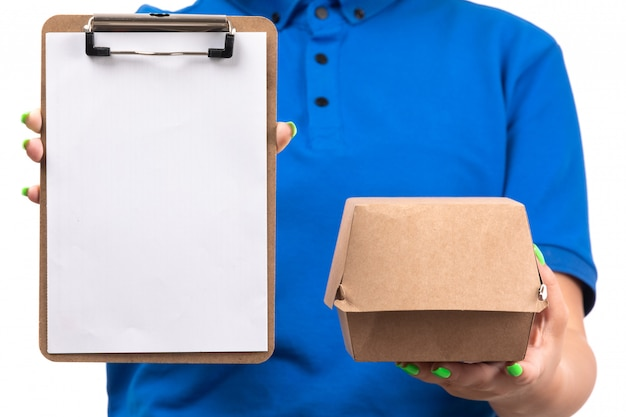 Widok z przodu młoda kobieta kurier w niebieskim mundurze, trzymając pakiet dostawy żywności i notatnik do podpisów