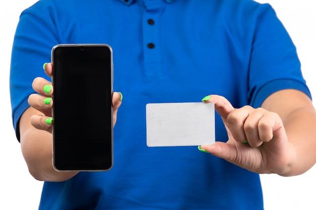 Widok z przodu młoda kobieta kurier w niebieskim mundurze trzymając telefon i białą kartę