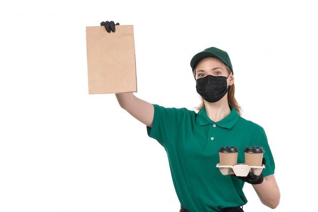 Widok z przodu młoda kobieta kurier w zielonych jednolitych czarnych rękawiczkach i czarnej masce, trzymając filiżanki i opakowanie