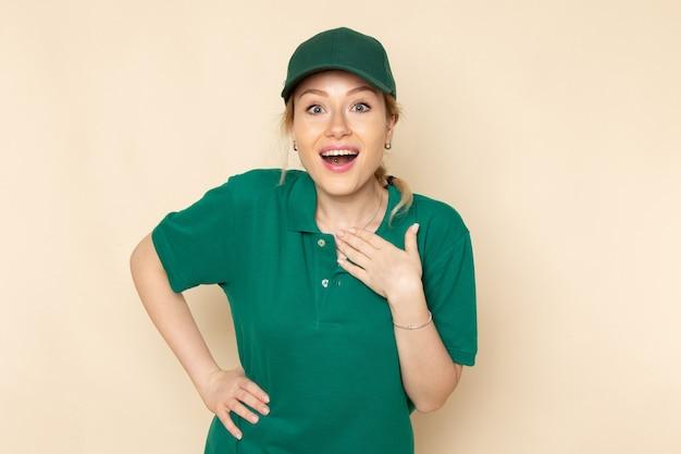 Widok z przodu młoda kobieta kurier w zielonym mundurze i zielonej pelerynie pozowanie i uśmiechając się na kremowym mundurze pracy kobiety