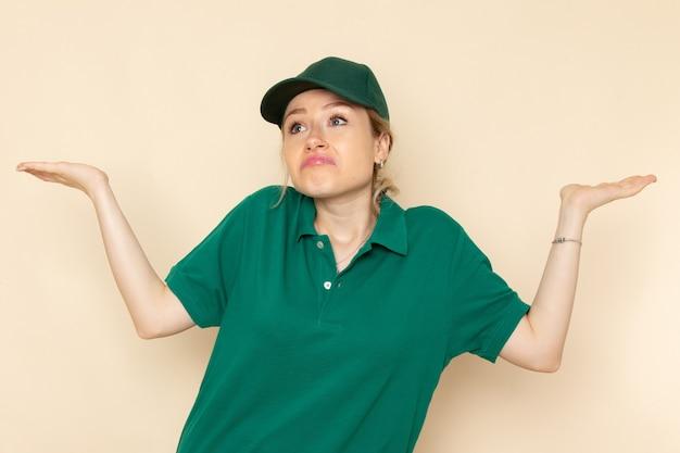 Widok z przodu młoda kobieta kurier w zielonym mundurze i zielonej pelerynie pozowanie na kremowym mundurze kobiety