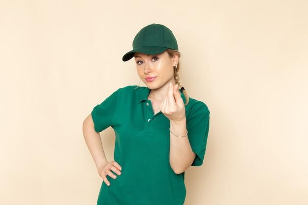 Widok z przodu młoda kobieta kurier w zielonym mundurze i zielonej pelerynie pozowanie na lekkiej przestrzeni mundur pracy kobiet