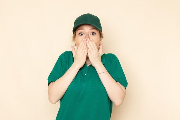 Widok z przodu młoda kobieta kurier w zielonym mundurze i zielonej pelerynie pozowanie na lekkiej przestrzeni mundurze pracownika kobiety