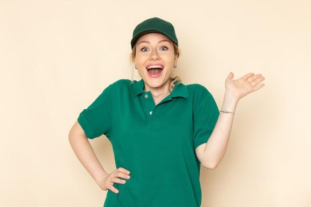 Widok z przodu młoda kobieta kurier w zielonym mundurze i zielonej pelerynie pozuje i uśmiecha się na jasnej przestrzeni