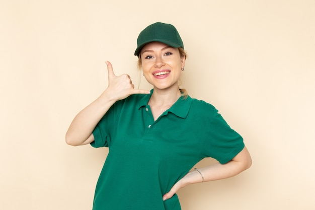Widok z przodu młoda kobieta kurier w zielonym mundurze i zielonej pelerynie pozuje i uśmiecha się na lekkim mundurze pracy w kosmosie