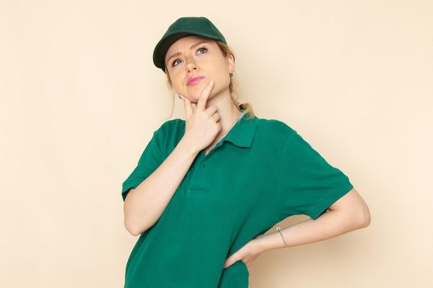 Widok z przodu młoda kobieta kurier w zielonym mundurze i zielonej pelerynie pozuje na lekkim mundurze pracy kobiety