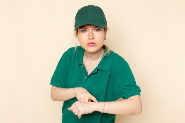 Widok z przodu młoda kobieta kurier w zielonym mundurze i zielonej pelerynie pozuje na lekkim mundurze pracy w kosmosie