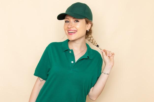 Widok z przodu młoda kobieta kurier w zielonym mundurze i zielonej pelerynie pozuje z uśmiechem na lekkiej kosmicznej dziewczynie