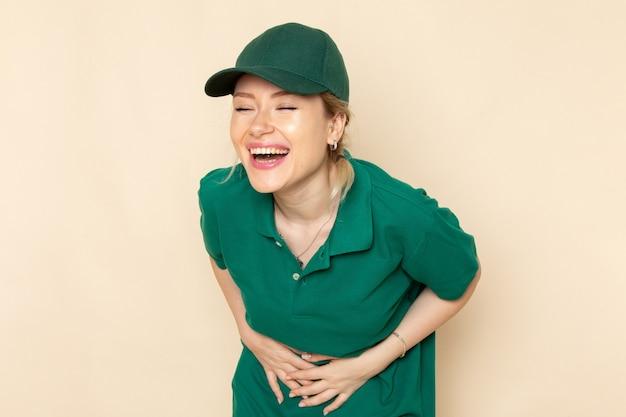 Widok z przodu młoda kobieta kurier w zielonym mundurze i zielonej pelerynie śmiejąc się na lekkim mundurze pracy kobiety