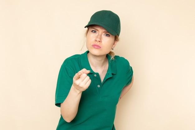 Widok z przodu młoda kobieta kurier w zielonym mundurze i zielonej pelerynie stwarzających zagrożenie na lekkim mundurze pracy kobiety