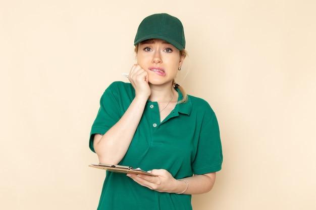 Widok z przodu młoda kobieta kurier w zielonym mundurze i zielonej pelerynie trzyma notatnik z przestraszonym wyrazem na jasnej przestrzeni