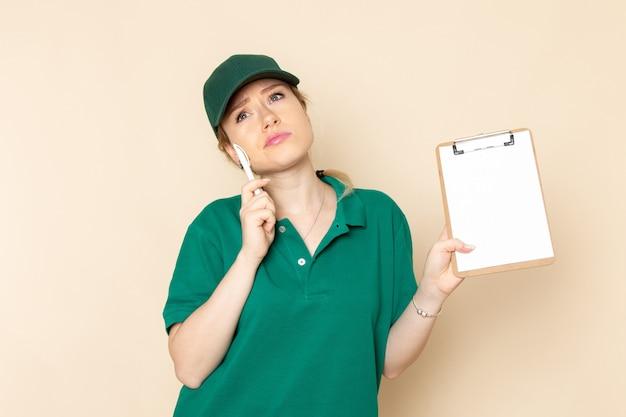 Widok z przodu młoda kobieta kurier w zielonym mundurze i zielonej pelerynie trzymając notatnik, myśląc na lekkiej przestrzeni