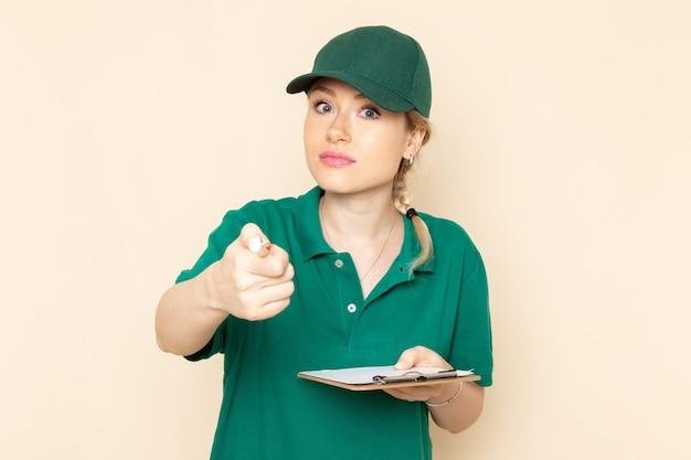 Widok z przodu młoda kobieta kurier w zielonym mundurze i zielonej pelerynie trzymając notatnik na lekkiej przestrzeni