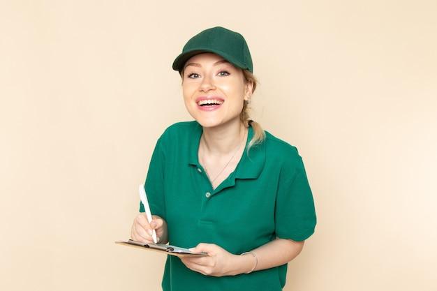 Widok z przodu młoda kobieta kurier w zielonym mundurze i zielonej pelerynie trzymając notatnik uśmiechając się na lekkiej przestrzeni