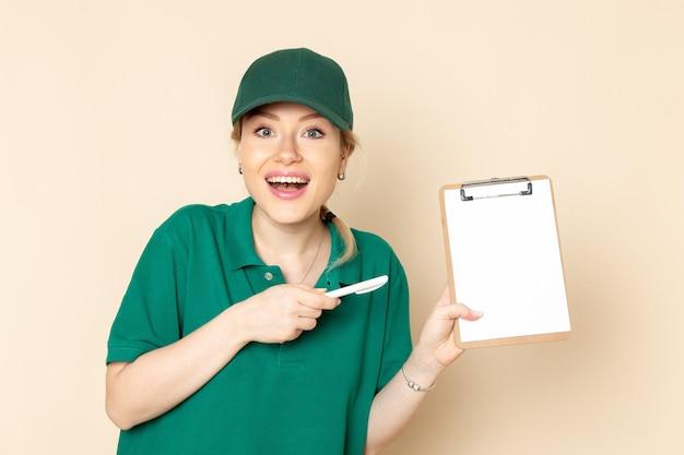 Widok z przodu młoda kobieta kurier w zielonym mundurze i zielonej pelerynie trzymając notatnik uśmiechnięty na jasnej podłodze