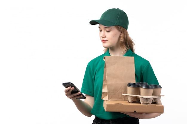 Widok z przodu młoda kobieta kurier w zielonym mundurze, trzymając filiżanki kawy opakowania żywności za pomocą telefonu