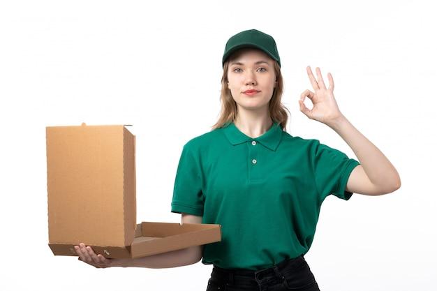 Widok z przodu młoda kobieta kurier w zielonym mundurze trzymając pakiet dostawy żywności